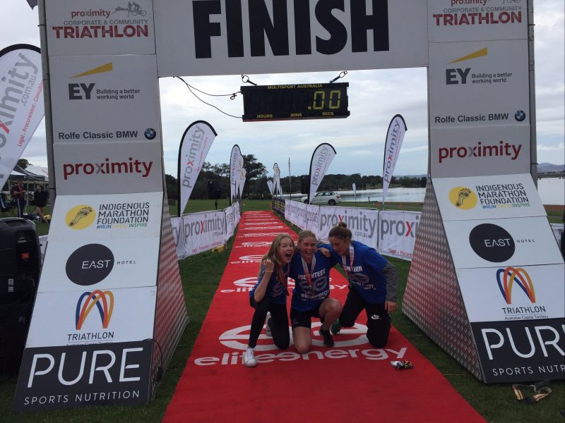 Children pose underneath the finish sign