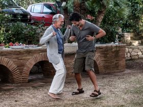 Two older men dance together in the driveway of an Italian home