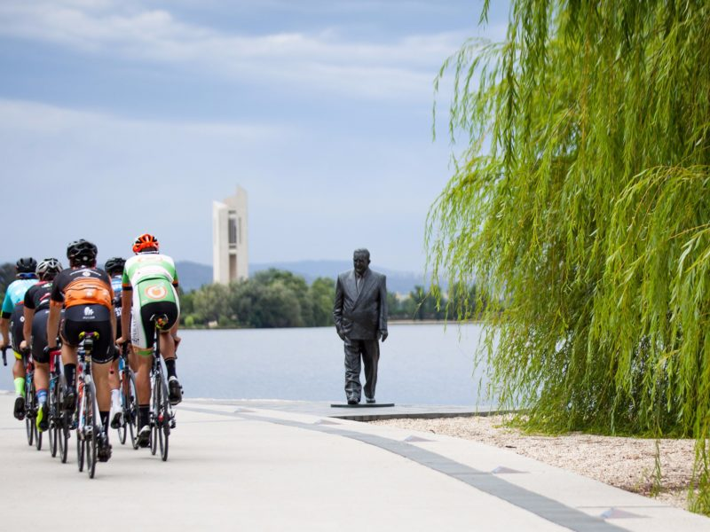 Group of cyclists going past the R G Menzies statue on the Lake Burley Griffin foreshore