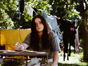 Photograph of Ruby Fields sitting at desk outdoors