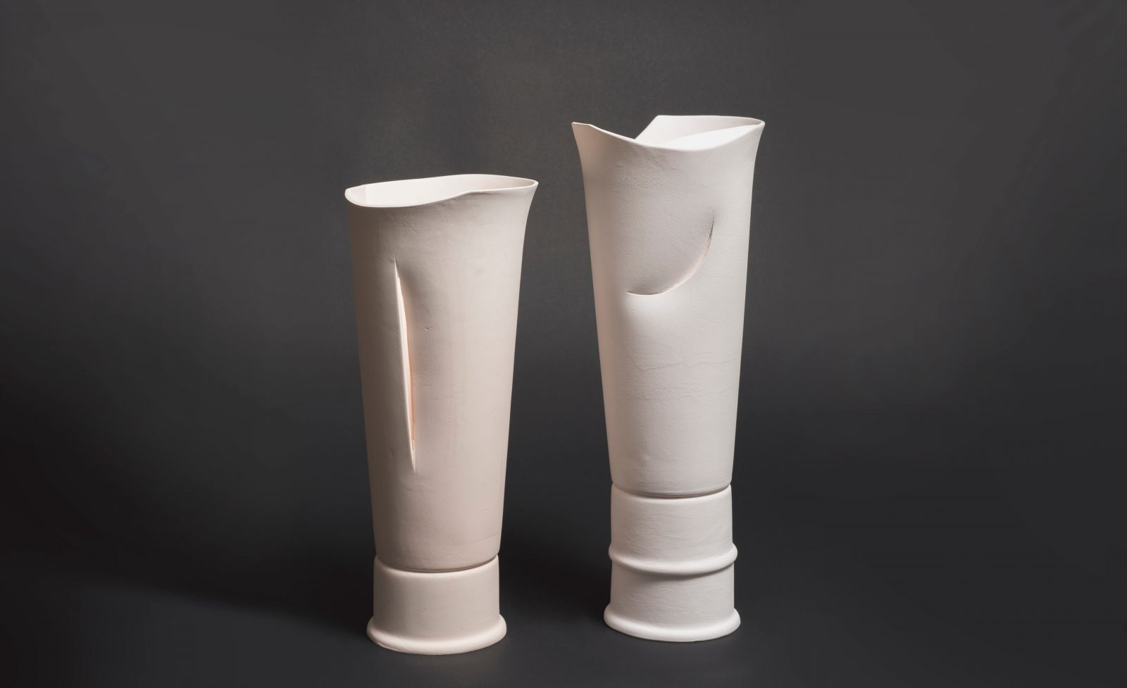 Image of two vases, thin with slits.