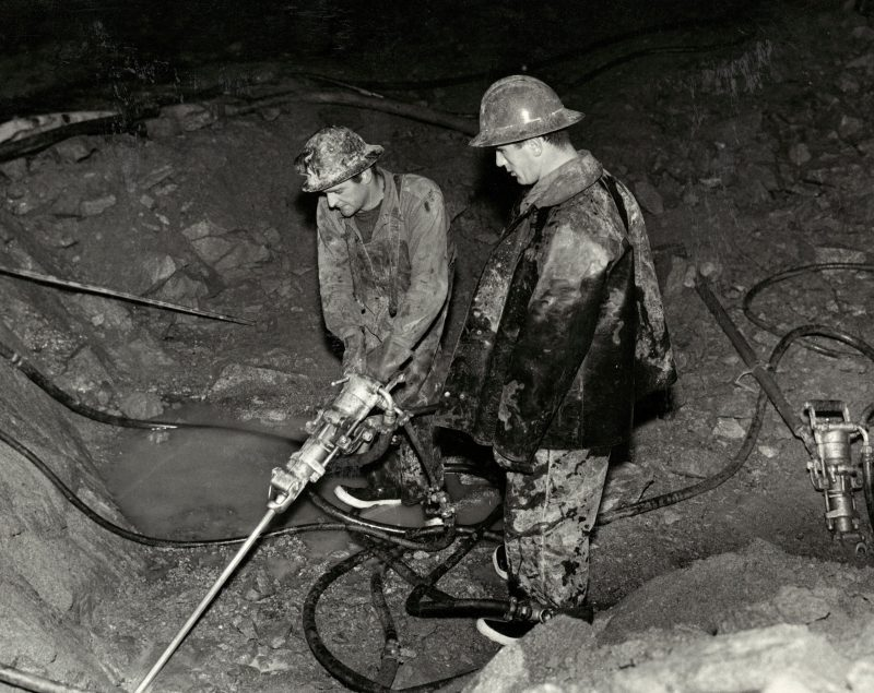 A black and white photo of two men in work gear with a large drill.