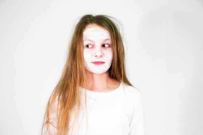 Girl wearing a white t-shirt on a white background with white face paint on