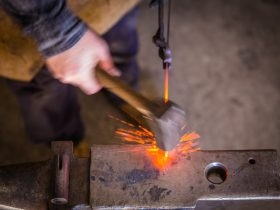 blacksmith striking hot metal on an anvil with sparks flying