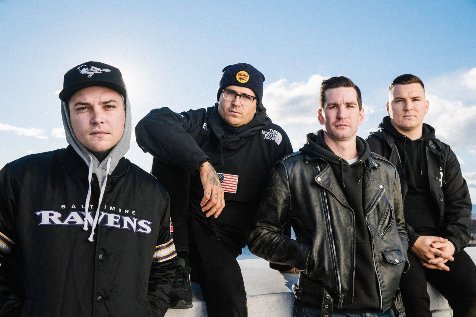 Photograph shows the four members of The Amity Affliction looking moody in front of a blue sky