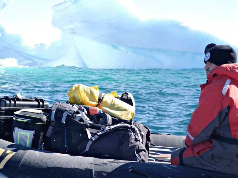 An Antartic scientist in a boat on the water, with a large iceberg in the background