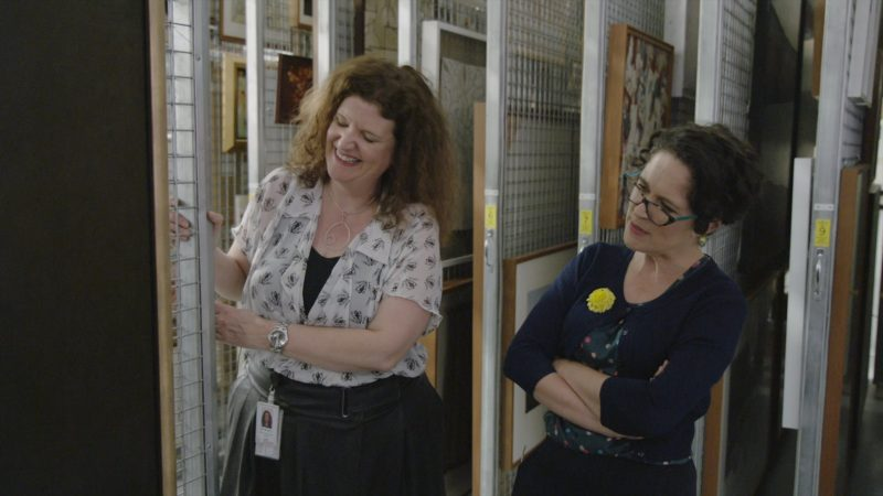 Justine Van Mourik and Annabel Crabb look at a piece of art in the art store