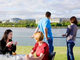 People eating on the deck overlooking the lake and national attractions