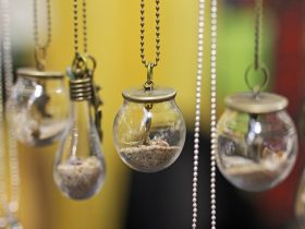 Small glass bulb pendant necklaces filled with sand and trinkets at the Old Bus Depot Markets