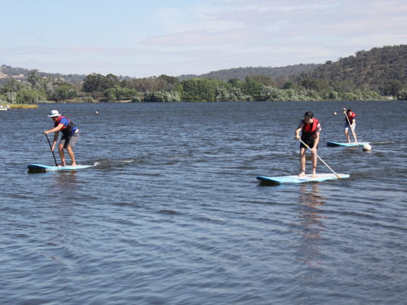 Three people paddleboarding on Lake Burley Griffin