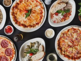 Flatlay of pizza and pasta dishes on black background