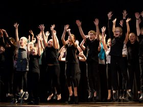 Members of Junior Albatross Musical Theatre Company jumping with joy at being onstage