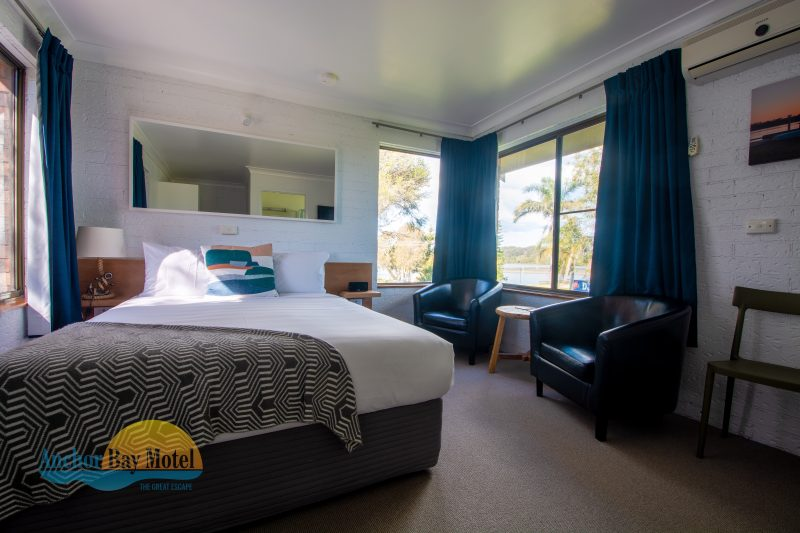 The deluxe room offers a comfy queen bed, seating area, and kitchenette facilities.