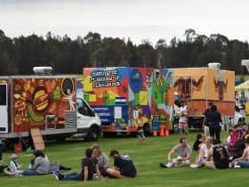 Food trucks surrounded be people siting on grass
