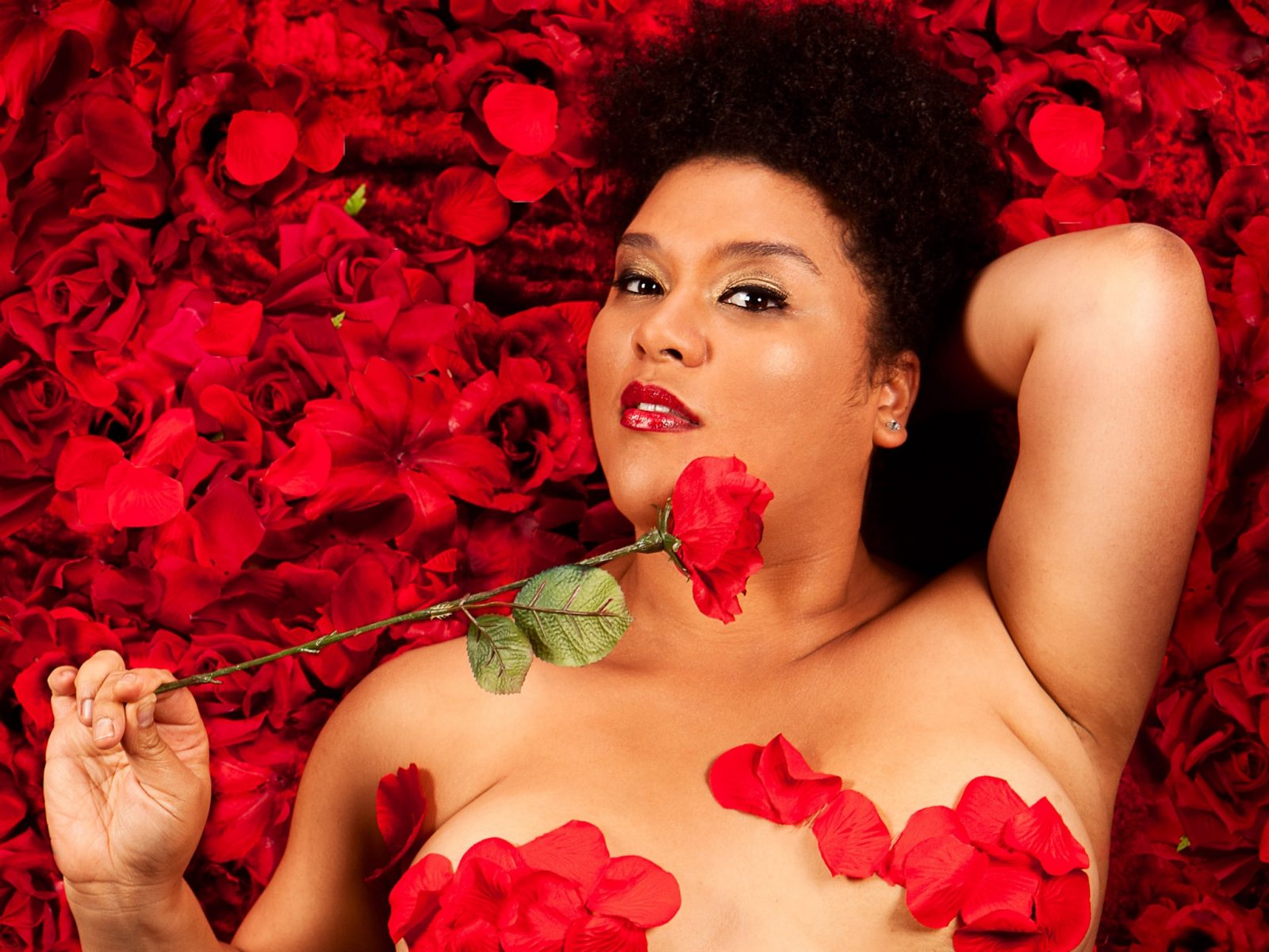 Candy Bowers lying on red rose petals