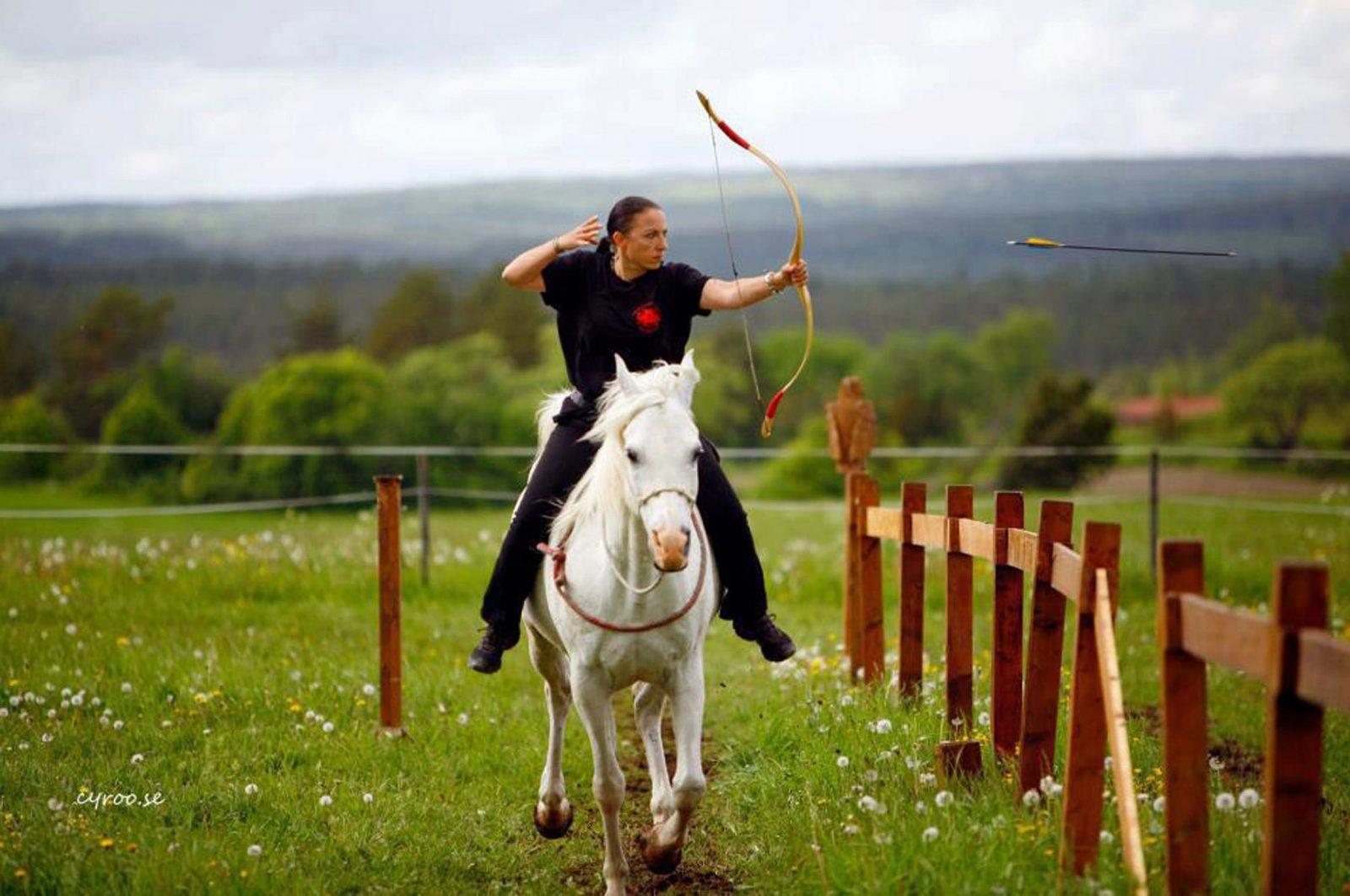 Woman on horseback shooting arrows