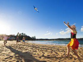 Family flying a kite on Avoca Beach, Central Coast