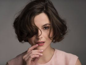 A young woman with short hair looking seductively straight to camera.