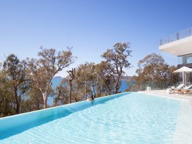 Turquoise wet-edge infinity pool with swimmer looking out across bay
