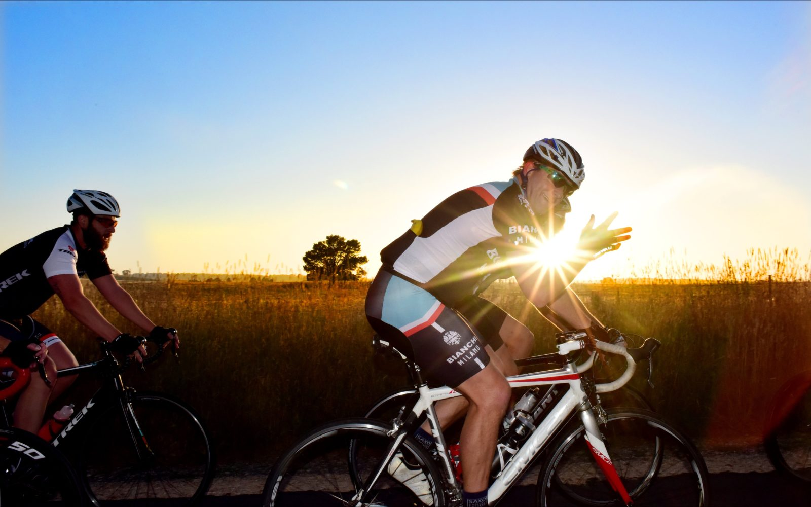 Cyclist waving to the camera at dusk