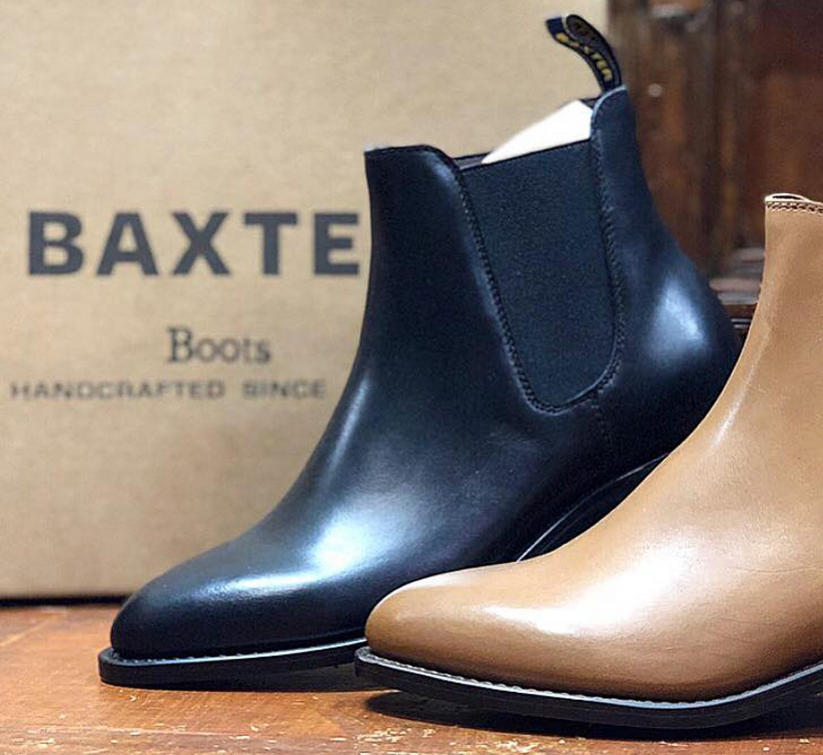 1 tan and 1 black boot in front of a Baxter box