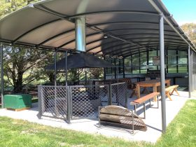 Communal area with firepit, banquet seating and BBQ