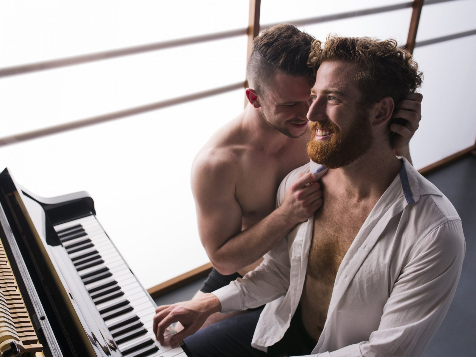 Image of two men at a piano, embracing.