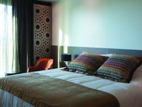 A king bed with white linen and colorful pillows