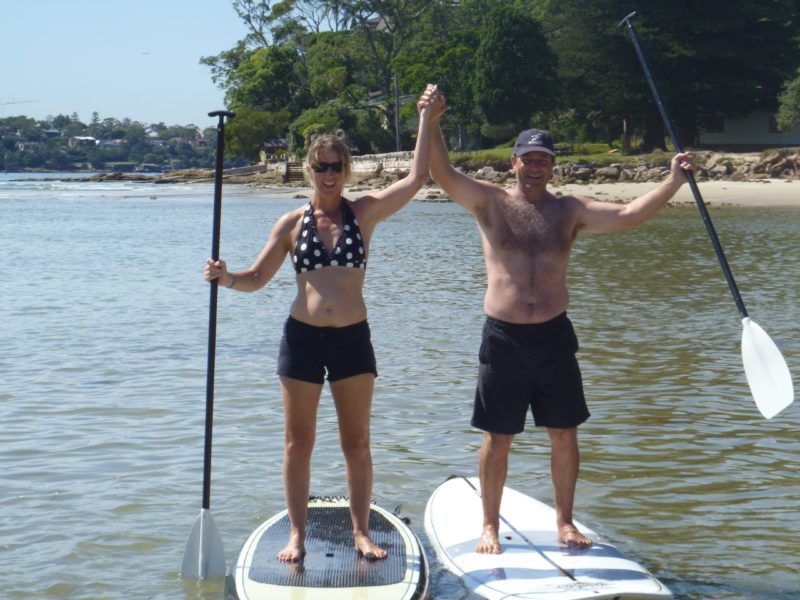 Guy and girl on stand up paddle boards at bundeena beach