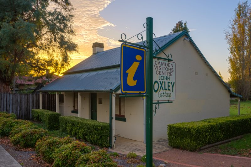Image of John Oxley Cottage, with the sun setting in the background.