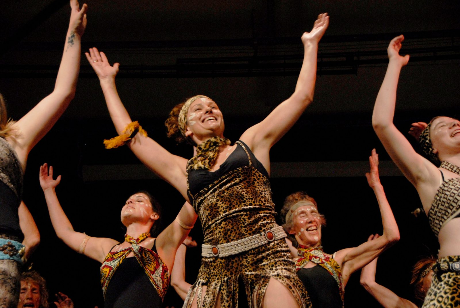 Woman upraised arms dancing in group