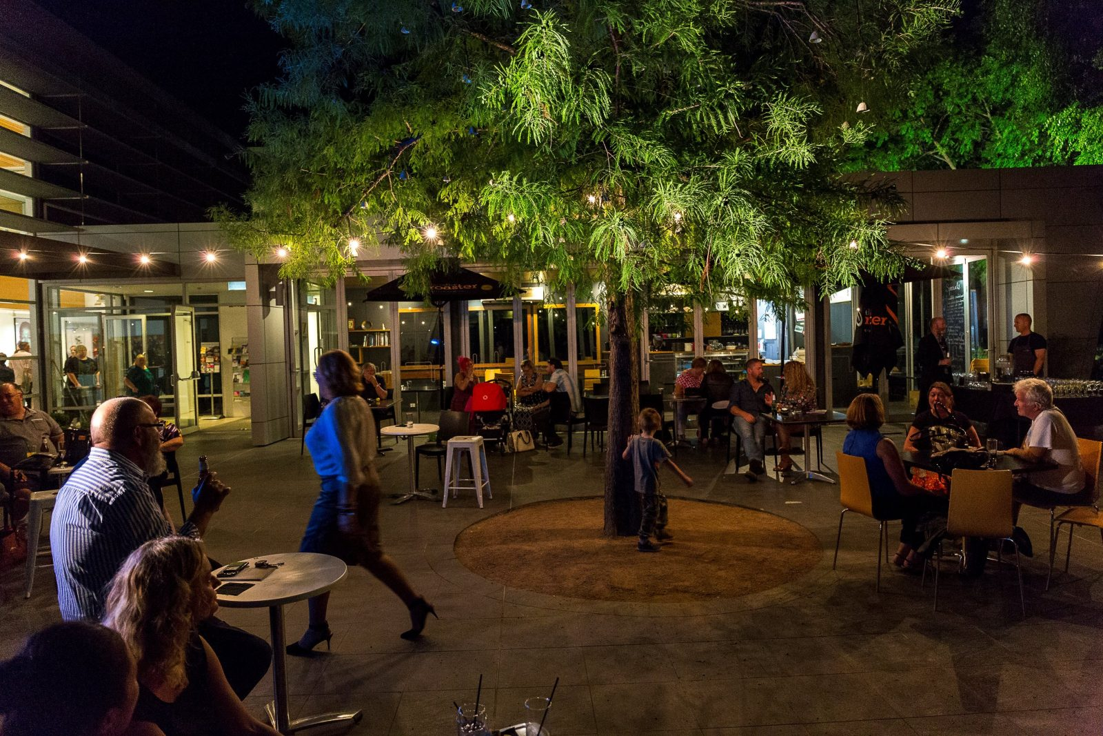 People eating and drinking in outdoor courtyard on summer evening