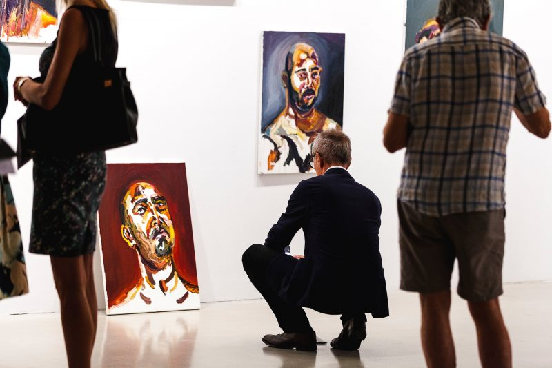 A man is squatting, viewing a portrait leaning on the wall