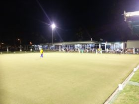 group of people doing lawn bowling at night