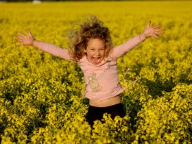 Excited girl in canola field with arms wide open