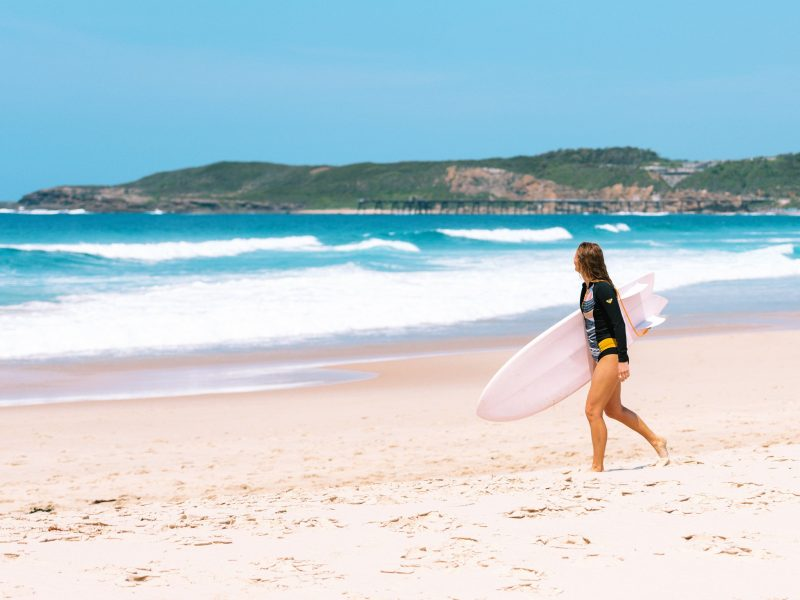 Girl entering the surf at with Catherine Hill Bay jetty in background