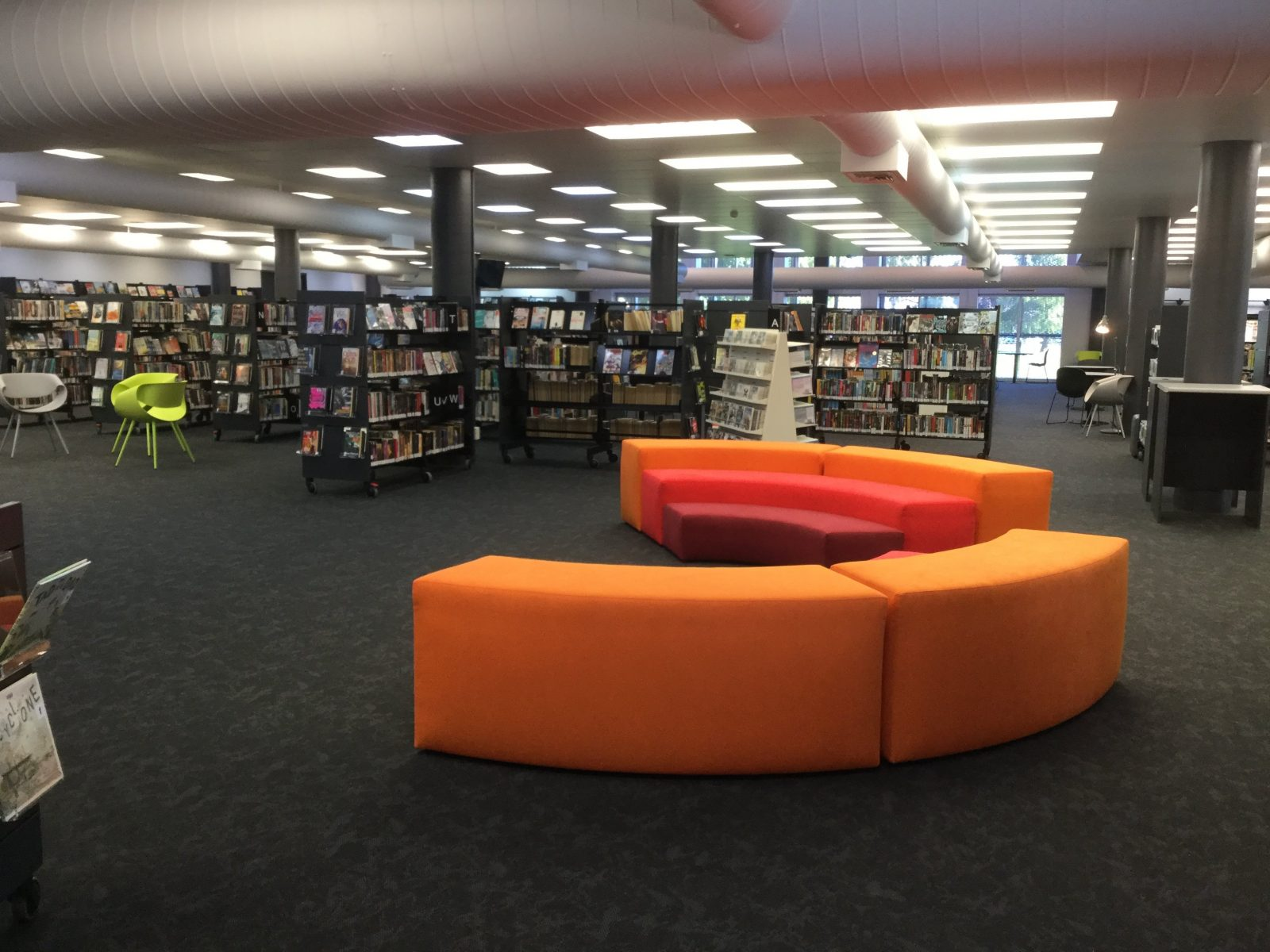 Brightly coloured lounge in the foreground with books on shelving behind it.