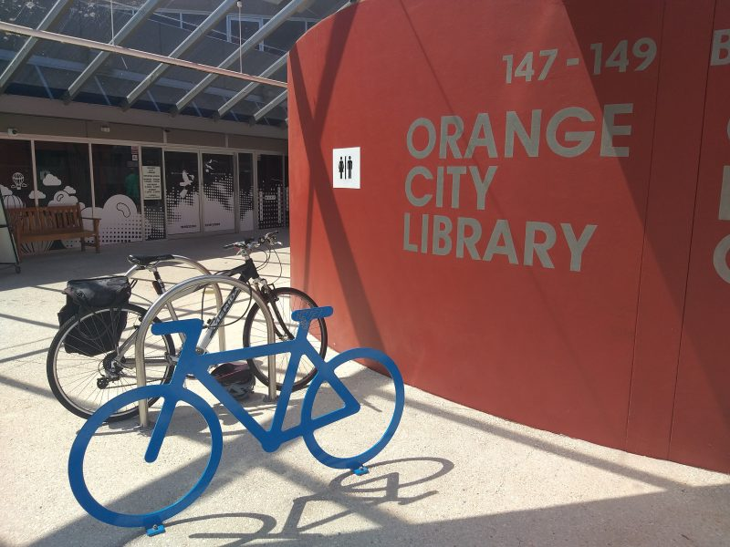 Blue bike rack shaped like a bicycle in front of red wall at the front of Orange City Library sign.