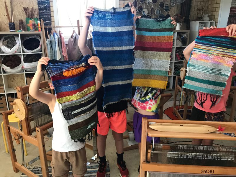 children showing off their weaving projects