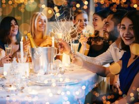 Christmas celebrations with a group of people with beverages and fairy lights in the background.
