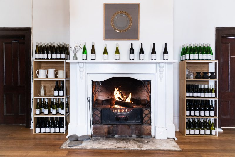 A blazing fire is surrounded by shelves of wines and awards in the historic Old Collector Inn.