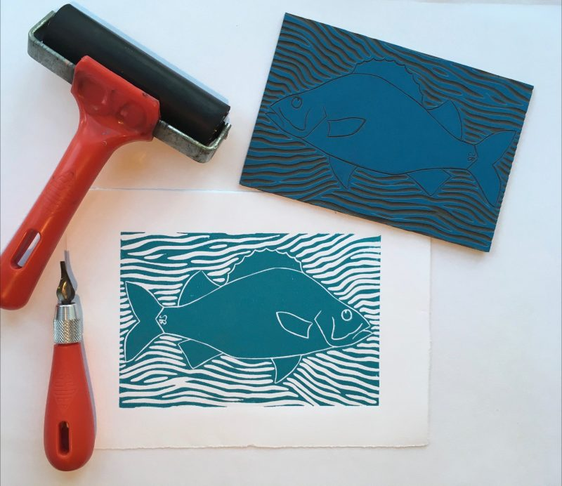 Blue printed image of a fish, printing roller, lino cutter and lino block printing tile