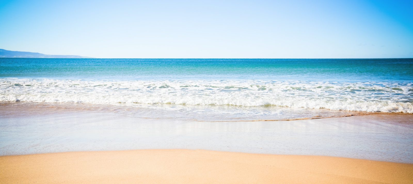 Pristine blue water and golden sand with gentle waves