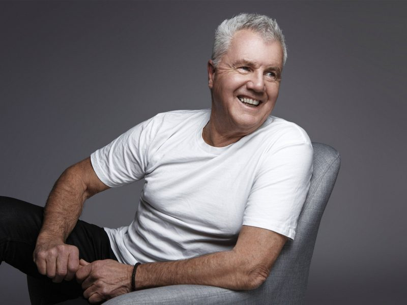 Daryl Braithwaite relaxed promotional shot wearing black jeans and white shirt