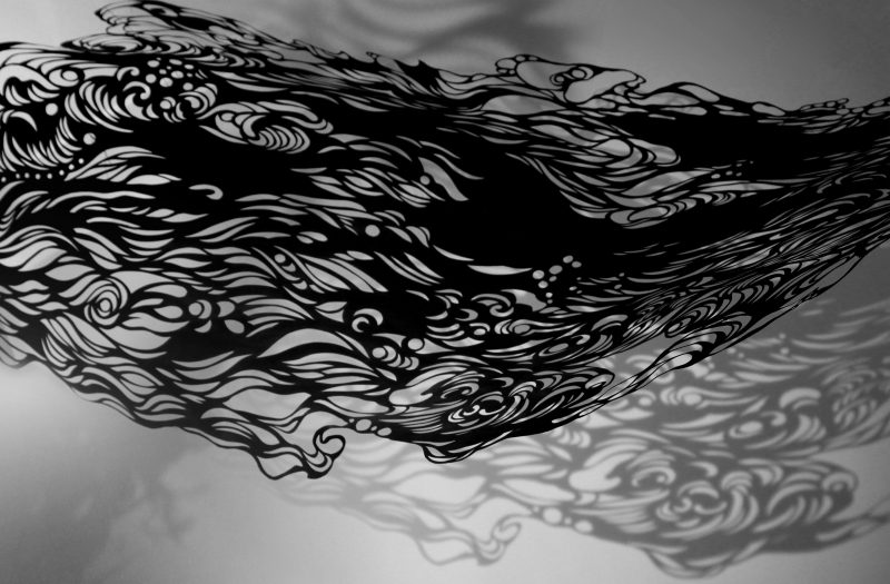 Image of paper sculpture by artist Tianli Zu. A black piece or paper that has been intricately cut.