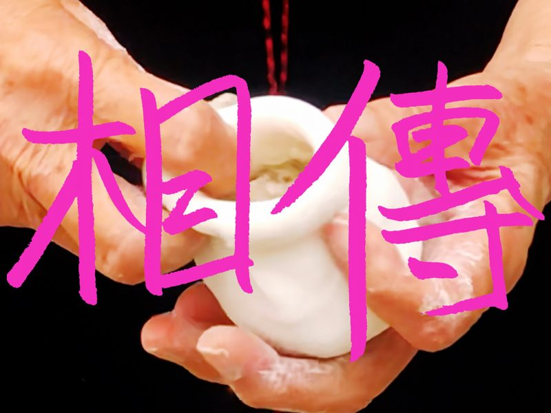 Pink Chinese text on top of a pair of hands modelling a form using clay.