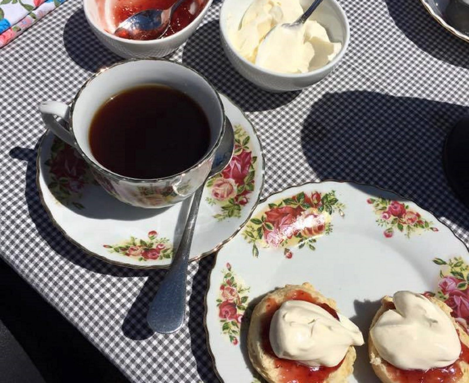 Plate of scones with jam and cream and a cup of black tea