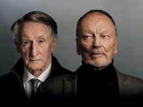 Two older men side by side, one looking to the side suspiciously and one looking straight on.