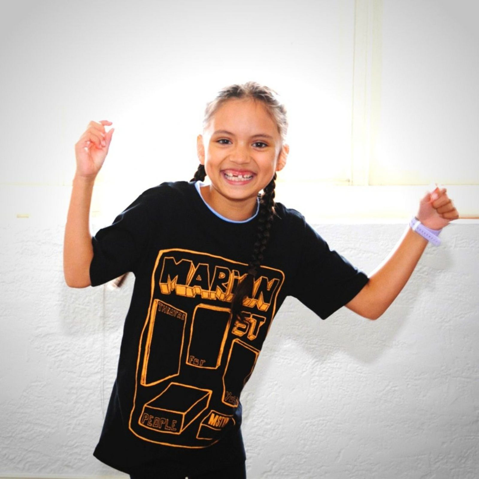 A girl grins and raises her arms like a bear. She wears a black t-shirt against a white background.