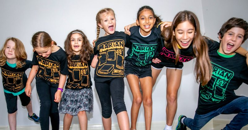 Kids leaning on each other and falling over. Wearing smiles and MSTYP t-shirts against a white wall.